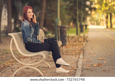 Charming woman sitting in the park and call someone with her phone #732765748
