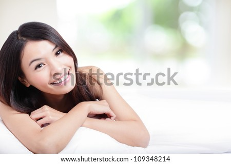 Charming woman Smile face close up and she lying on the bed in the morning with nature green background, model is a asian girl