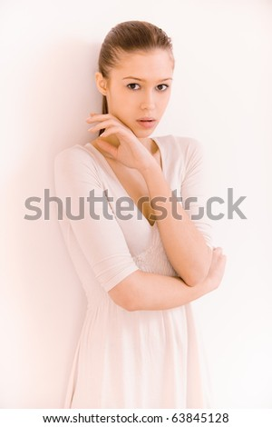 Charming woman stands at wall and thoughtfully looks.