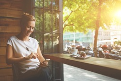 Charming woman with beautiful smile reading good news on mobile phone during rest in coffee shop, happy Caucasian female watching her photos on cell telephone while relaxing in cafe during free time