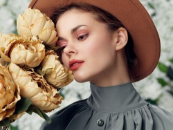 Charming woman with dry flowers and green shirt hat