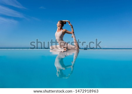 Charming woman yoga lover in overalls makes Mermaid Pose or Eka Pada Rajakapotasana asana by pool while relaxing at sea in sunny warm country. The concept of relaxation and better health. Copyspace