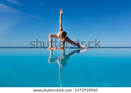 Charming woman yoga lover in overalls makes Uthit Triconasana by the pool while relaxing at sea in a sunny warm country. The concept of relaxation and better health. Copyspace
