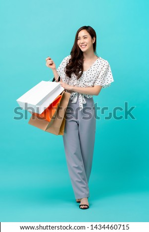 Charming young Asian woman happily shopping during sale season isolated on light blue studio background