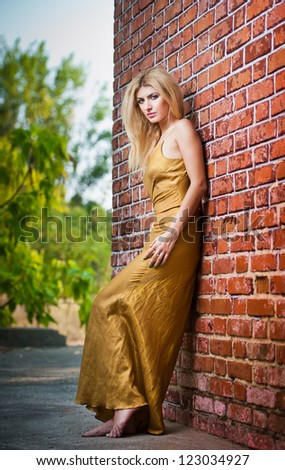 Charming young blonde woman in yellow dress near the brick wall.Sexy gorgeous young woman near old wall.Full length portrait of a blonde woman with long hair near a brick wall