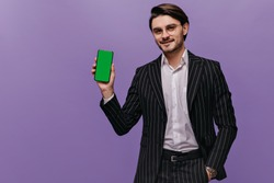 Charming young brunette with white shirt, black striped suit, looking straight forward, smiling and presenting mobile phone in one hand. Man posing against violet pastel background