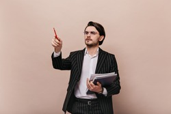 Charming young brunette with white shirt, striped suit, glasses, holding papers in one hand and pointing on free space by pencil. Man posing isolated over beige background