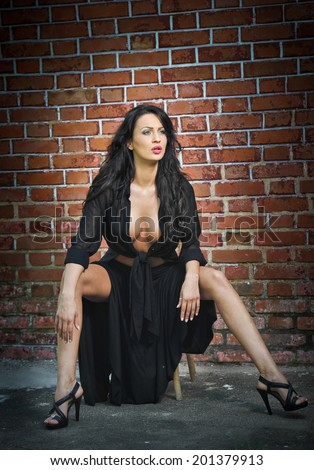 Charming young brunette woman in black and high heels near the brick wall. Sexy gorgeous young woman near old wall. Full length portrait of a provocative woman with long hair near a brick wall #201379913