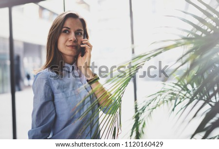Charming young business woman talking with partner via mobile phone while standing at modern business center