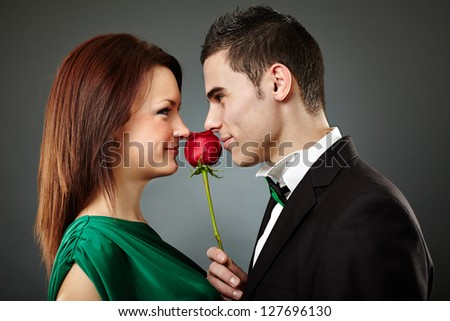 Charming young couple embracing over gray background. Valentine concept