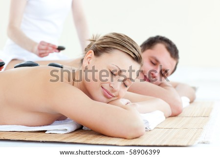 Charming young couple having a stone massage in a spa center #58906399