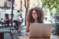 Charming young female caucasian freelancer in glasses is sitting in a street cafe with her netbook and looking aside; beautiful woman in eyeglasses in a bar outdoors with the laptop, a cyclist behind