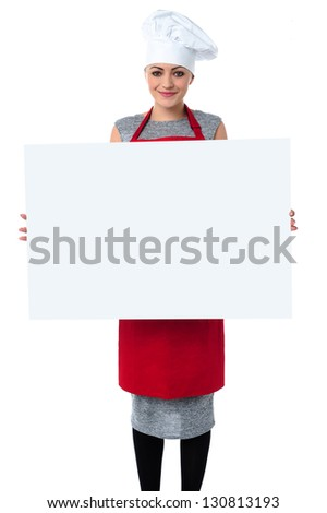 Charming young female chef displaying a blank advertising board.