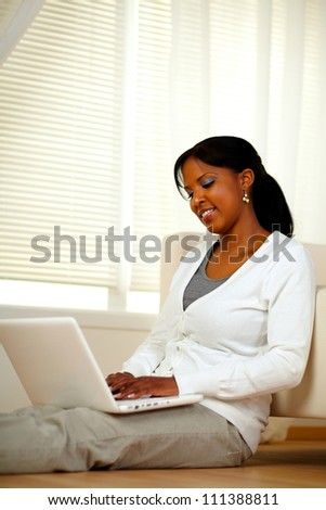 Charming young female working on laptop while sitting on the floor at home indoor. With copyspace
