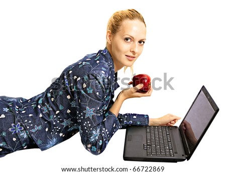 Charming young girl In dark blue suit is on floor, holds in hand big red apple. Workout on laptop computer and smile