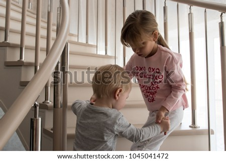 Charming young girl with long hair in home pajamas helps her younger brother to climb stairs in house. Expressive cute faces close-up and funny grimaces.  #1045041472