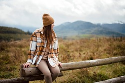 Charming young lady dressed in stylish warm outfit sitting on old wooden fence with amazing mountains view on background. Calmness and harmony among green nature.