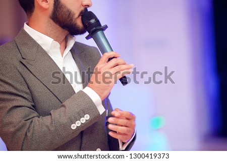 Charming young man leading acts at the evening concert in a gray suit under the light of the spotlights. Stock photo ©