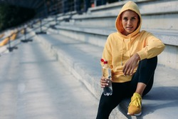 Charming young sportswoman in yellow sweater with hood on head holding water, sitting on steps and looking at camera. Healthy brunette relaxing after outdoor activity.