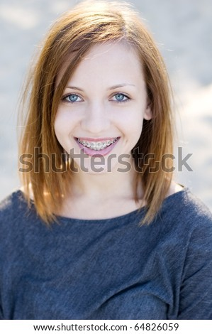 Charming young teenage girl wearing braces and smiling cheerfully