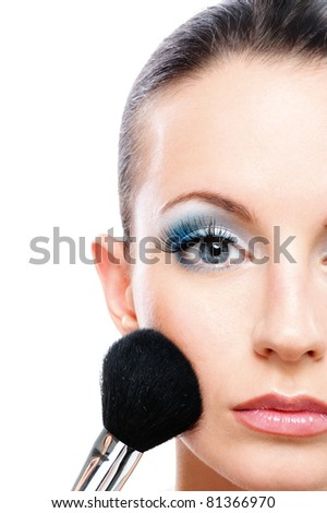 Charming young woman applying blusher close up.