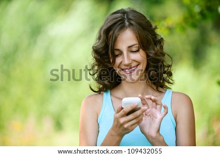 Charming young woman close-up in blue shirt reads message to mobile phone, against green of summer park.