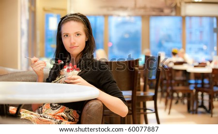 Charming young woman eats dessert in cafe.