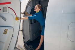Charming young woman flight attendant closing aircraft door and smiling
