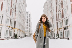 Charming young woman in coat with long brunette hair enjoying snowfall in big city. Cheerful emotions, smiling, christmas mood, positive face emotions, winter weather. Place for text