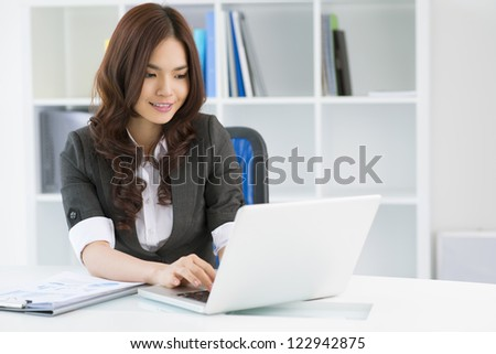 Charming young woman in formalwear computing in office