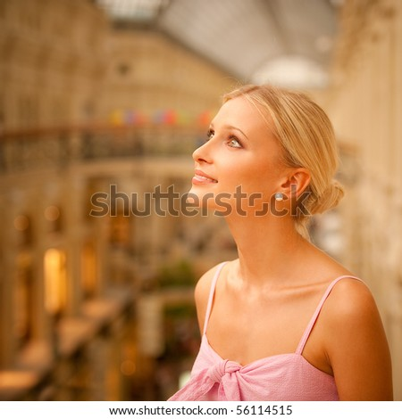 Charming young woman in huge hall leans against handrail.