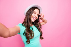 Charming young woman in white hat travel and take selfie on front camera smartphone showing v-sign isolated on shine pink background