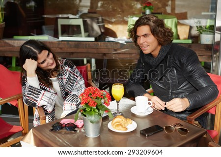 Charming young woman sitting in sidewalk cafe and breakfast with her best friend,two people enjoying and spending time together at pleasant conversation,couple of tourists taking break after city walk