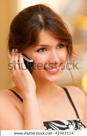 Charming young woman speaks by mobile phone and smiles.