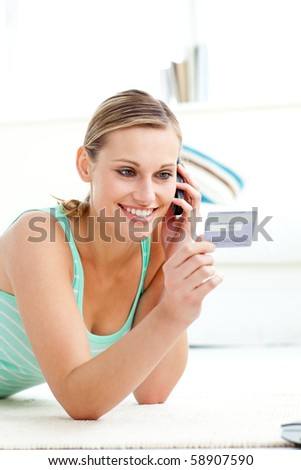Charming young woman talking on phone holding a card in the living room