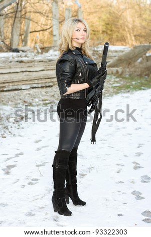 Charming young woman with a gun outdoors