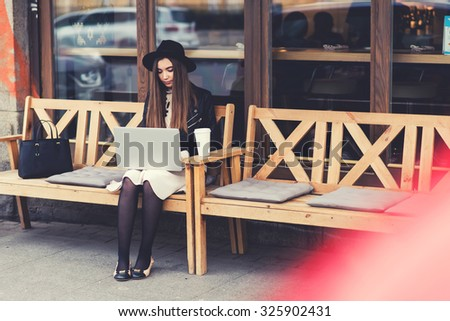 Charming young woman with trendy look work on portable laptop computer during coffee break outdoors,gorgeous female freelancer using net-book for remote job while sitting on the bench in sidewalk cafe