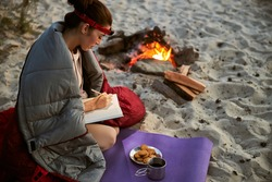 Charming young woman wrapped in sleeping bag writing in diary while sitting on yoga mat near bonfire