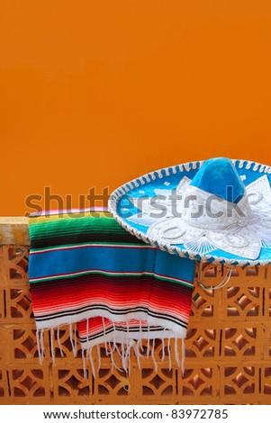 charro mariachi blue mexican hat and serape poncho over orange tiles wall