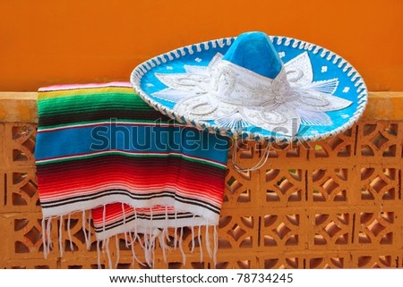 charro mariachi blue mexican hat serape poncho over orange tiles wall
