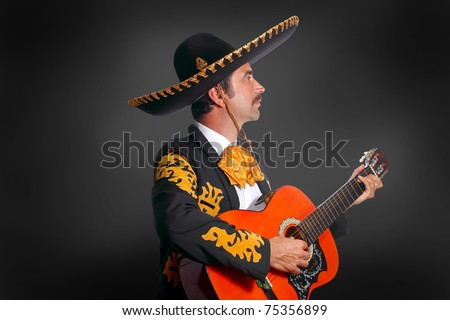 Charro Mariachi playing guitar on black background [Photo Illustration]