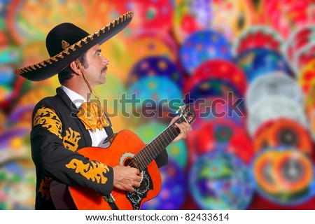 Charro Mariachi playing guitar over colorful blur handcrafts background  [Photo Illustration]