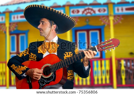 Charro Mariachi singer playing guitar in Mexico houses background [Photo Illustration]