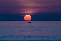 Charter Fishing Boat at Sunrise near Cocoa Beach, Florida, Capturing a Large Round Orange Sun Rising Above the Ocean Horizon