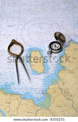 Charting the course. Antique navigation instruments on an old well used nautical chart Stock photo ©