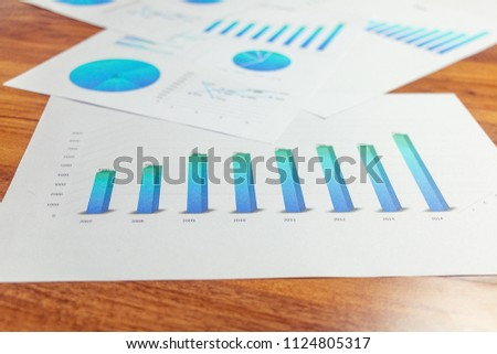 Charts and graphs are placed on the desks, data, and statistical performance of the company. #1124805317