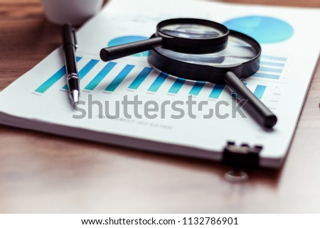 Charts and graphs.pen,Magnifying glass are placed on the desks, data, and statistical performance of the company in the past year. #1132786901