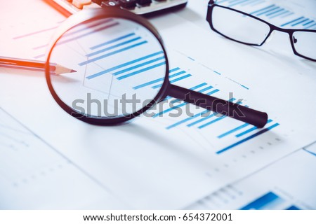 charts and graphs with magnifying glass and pencil, calculator, clock. Reflection light and flare. Concept image of data gathering and statistical working.  #654372001