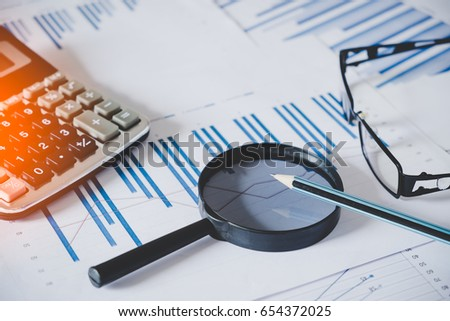 charts and graphs with magnifying glass and pencil, calculator, clock. Reflection light and flare. Concept image of data gathering and statistical working.  #654372025