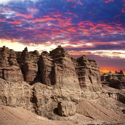 Charyn grand canyon in Kazakhstan at sunset dramatic sky background in purple, red and blue colors